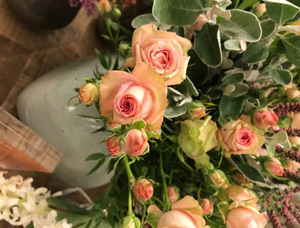 Close up of peachy pink roses in green vases