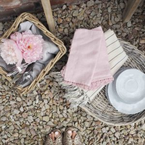 Pink napkins and tableware in wicker baskets