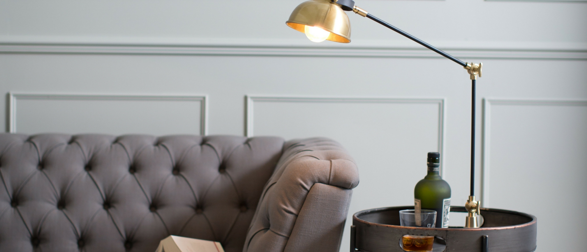 Grey sofa with table lamp and side table