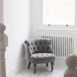 Soft grey button back chair against radiator
