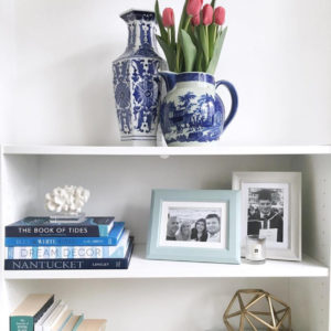 Open white shelves with decorative coral and ceramic blue vase