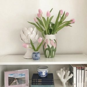 White shelving and pink tulips in vase