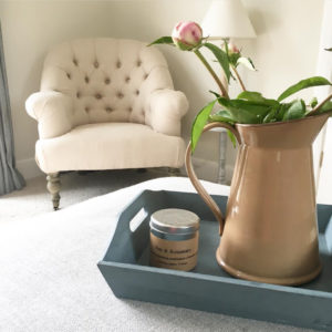 Upholstered chair and flowers in jug